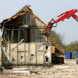Stock Photo: Excavator demolishing a building