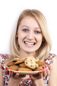 Young grimacing woman with plate of cookies isolated — Stock Photo
