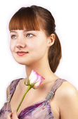 Portrait of young smiling woman with pink rose — Stock Photo