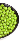 Preserved peas in black bowl isolated — Stock Photo