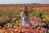 Bonita rubia en un campo de flores — Foto de Stock
