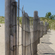 Wooden Beach Fence on Sand Dunes with Clear Blue Sky - Stock Photo