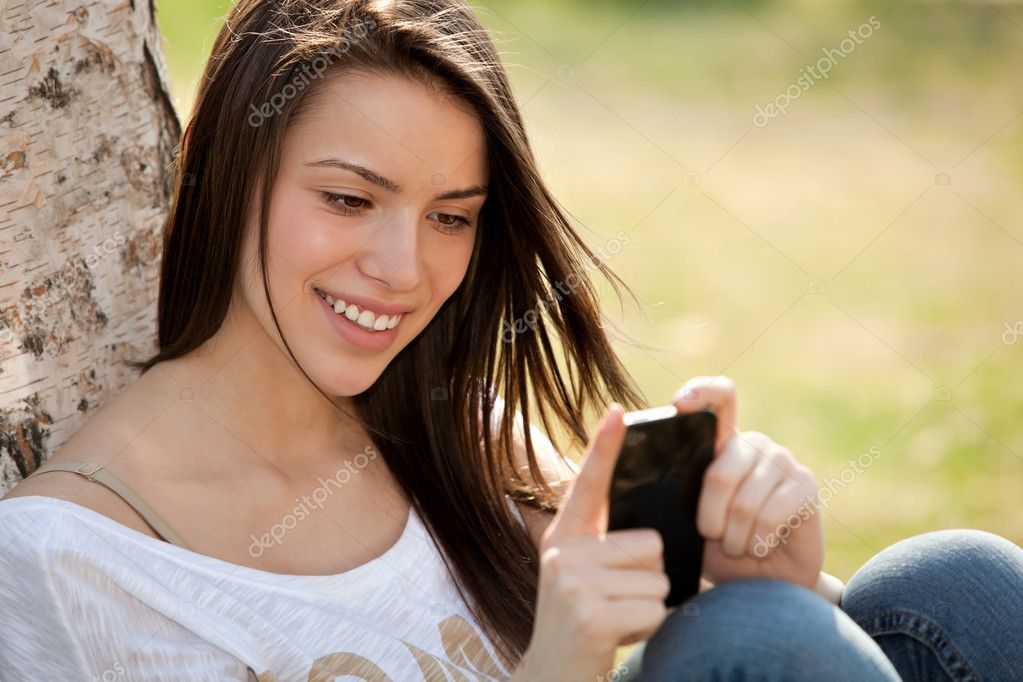 Happy young woman looking at her phone  Stock Photo #10041753