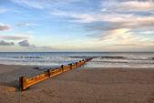Kumlu sahilde ahşap dalga kesicisi — Stok fotoğraf