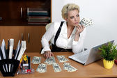 Attractive business woman sitting at a table and holding a dolla — Stock Photo