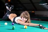 Sexy woman lying on billiard table in pool club — Stock Photo