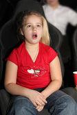 Little girl sitting on armchairs at cinema — Stock Photo