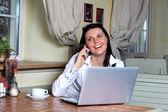 Young attractive business woman working on her laptop and talkin — Stock Photo