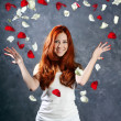 A very happy and joyfully girl tossing rose petals in the air — Stock Photo