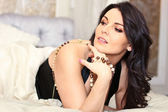 Portrait of beautiful brunette woman lying on bed — Stock Photo