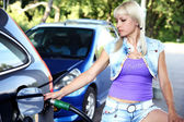 Young woman with fuel nozzle on gas station with black car — Stock Photo