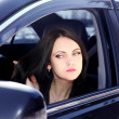 Stock Photo: Woman sitting in the car and looks in the mirror