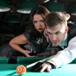 Portrait of a couple playing snooker in a dark club — Stock Photo #9555173