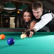 Portrait of a couple playing snooker in a dark club — Stock Photo