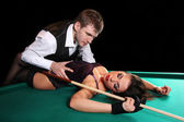 Girl lying on the table for a game of pool and a man hugging her — Stock Photo