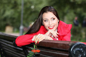 Young woman sitting on a bench in the park and in the hands hold — Stock Photo