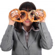 Young woman looking through pretzel - Stock Photo