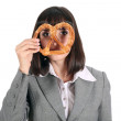 Young woman looking through pretzel — Stock Photo