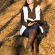 Girl reading in autumn forest — Stock Photo