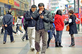 Two men using mobile phone on a busy pedestrian shopping street — Stock Photo