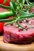 Raw beef steak on wooden board — Stock Photo