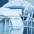 Clean plates and forks inside dishwasher — Stock Photo