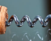 Corkscrew and cork on a glass table — Stock Photo