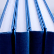 Stock Photo: Four blue notepads isolated close up