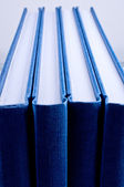 Four blue notepads isolated close up — Zdjęcie stockowe