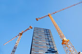 Skyscraper with tower cranes — Stock Photo