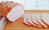 Ham cut into slices on a wooden board — Stock Photo