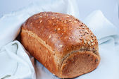 Loaf of bread on white satin fabric — Stock Photo