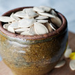 Ceramic bowl full of pumpkin seeds on kitchen table — 图库照片