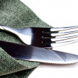 Knife and fork on green napkin - Stock Photo