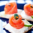 Canapes with smoked salmon on dark blue plate - Stock Photo