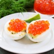Eggs and caviar on white saucer - Stock Photo