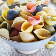 Multi colored pasta in bowl on coarse cloth - Stock Photo