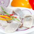 Herring bites with onion and pepper - Stock Photo