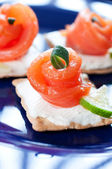 Canapes with smoked salmon on dark blue — Stock Photo