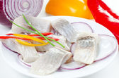 Herring bites with onion and pepper — Stockfoto
