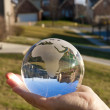 My world. Glass globe reflecting a street and blue sky. — Stock Photo