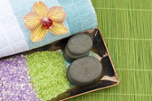 Spa concept with mineral bath salt, massage stones, towel and or — Stock Photo