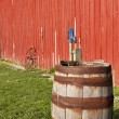 Stock Photo: Old wooden barrel beside red barn.