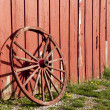 Old rustic wagon wheel beside a red barn. — Stock Photo #9776137