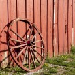 Old rustic wagon wheel beside a red barn. — Stock Photo