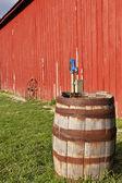 Oude houten vat naast een rode schuur. — Stockfoto