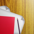 Red notebook and white paper with pencils isolated on wooden background — Stock Photo