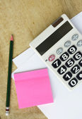 White paper with calculator pencil and memo on wood table — Stock Photo