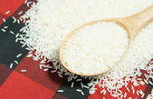 Rice grain and wooden spoon — Stock Photo