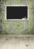 Empty blackboard with wooden frame and chalks on wall room — Stock Photo